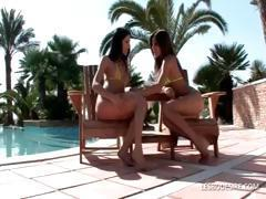Two hot lesbians fondle and suck titties outside by the pool