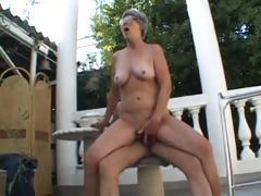 Granny is outside sucking on a younger cock and getting fucked