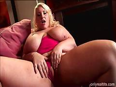 Scarlet Rouge is a big busty babe sitting on the couch masturbating