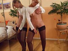 Girl in stockings rubs her pussy in front of a mirror and uses dildo