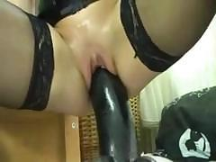 This horny MILF is using a huge black dildo in her wet pussy