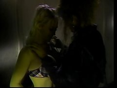 Lesbians lick and dildo each other in a dark room