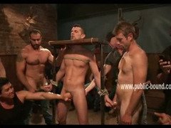 Man is bound in a medieval device, tied up and forcefully jerked off by dominatig men