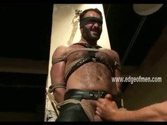 Rugged man is bound in leather and blindfolded by a dominating man that hits his chest