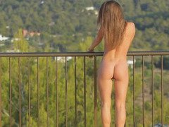 Hot brunette strips on terrace and performs a show
