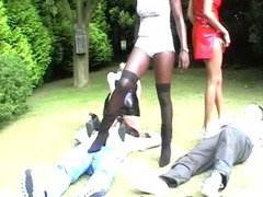 A trio of ladies dominate and facesit two men in the garden
