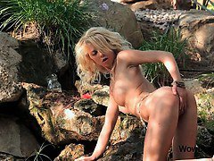Outdoor solo masturbation scene with curly blonde