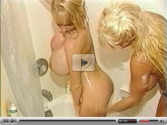 Two Busty Girls in the tub soaping up.