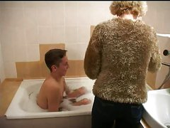 Older woman gives young man bath