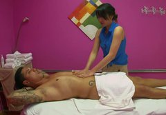 Sexy Asian girl massages tattooed guy and oils up his body