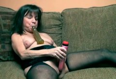 Nasty black haired MILF with saggy boobs masturbates on couch