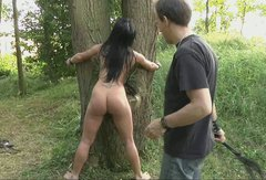 Slender nude brunette is tied up and fucked in the forest