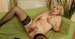Spoiled grannie in sexy black stockings fingers her wet pussy