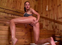Oiled long legged brunette gets rid of lingerie to tickle her pussy