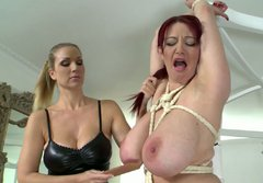 Cruel mistress spanks her slave girl's tits with a wooden paddle
