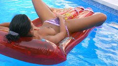 Brunette teen masturbates on the waves of pool