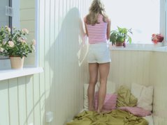 Cute blonde girl haves fun on the balcony