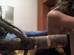 Topless girl tries to cut a Christmas tree with a knife