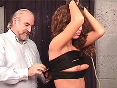 Bondaged longhaired slim brunette stands as master tightly ropes her small tits