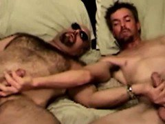 Mature duo in bed tugging together