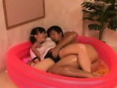 Asian schoolgirl sits in a plastic pool and gets her cunny