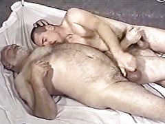 A younger men and older man playing with each other dick