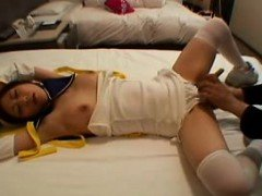 Pretty Japanese girl lies on the bed and is made to reach h