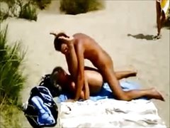 Naked couple fucks on the beach in front of strangers