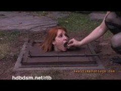A cute redhead slave gets covered with mud and piss outdoor