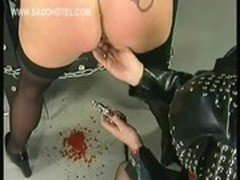 Dominatrix wearing latex spreads pussy lips of hot slave with metal clamps and spanks her on her ass