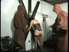 Hot naked slave with pierced pussy is tied and spanked on her great ass by master in a dungeon