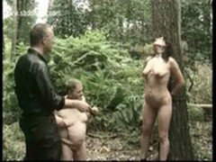 Slave tied to a tree is hit with a whip and master mastrubates her pussy while her husband is watch