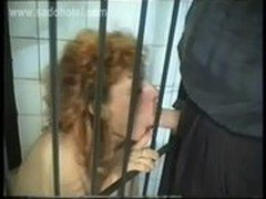 Horny slave with tiny tits sitting in a jail in a dungeon is sucking cock of her master