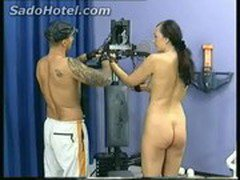 Beautiful brunette slave with nice tits and her clit pierced is tied to a fitness machine