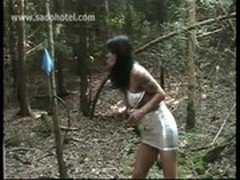 Slave tied on a tree gets hits with a whip by horny mistress