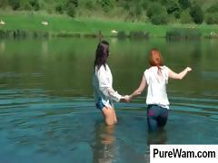 Two lesbians are having fun in a lake getting wet and horny