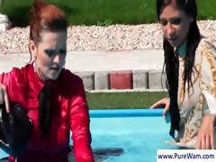 Redhead and brunette gals take a dip in the pool with their clothes on then strip