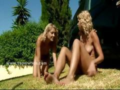 Pair of delicious blonde lesbians kissing outdoor on the grass in velvet sex